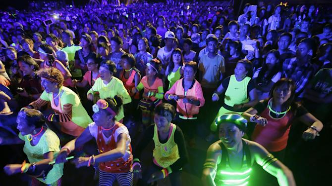Filipinos, wearing luminous shirts and bracelets, dance the Zumba during the symbolic switching off of the lights known as Earth Hour Saturday, March 28, 2015 in Quezon city northeast of Manila, Philippines. Earth Hour, participated in by more than 7,000 cities and townships worldwide, urges households and citizens to switch off their electricity for one hour to help reduce Carbon emissions to help save planet Earth. (AP Photo/Bullit Marquez)
