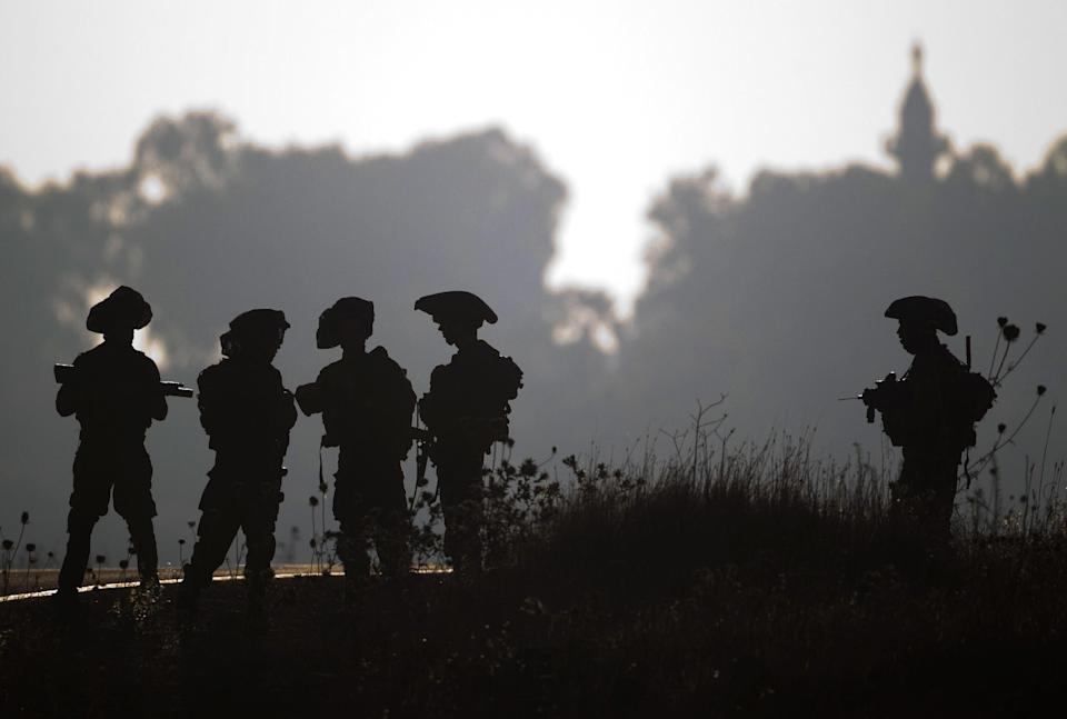 Israeli soldiers of the Golani brigade gather during training in the Israeli controlled Golan Heights near the border with Syria Wednesday, June 26, 2013. (AP Photo/Ariel Schalit)