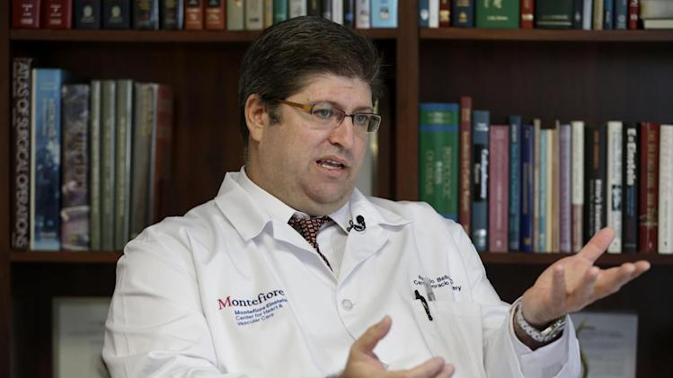 In this Thursday, Jan. 17, 2013 photo, Dr. Ricardo Bello speaks to a reporter at Montefiore Medical Center in New York. Bellow, a cardiac surgeon at Montefiore Medical Center, leads a program that aims to keep patients recovering from heart surgery from having to be rehospitalized. A new study shows parts of New York have among the nation's highest readmission rates. To help, Montefiore opened a clinic last fall to check on patients' recovery a week after they go home, and patients wear a bracelet with a 24-hour phone number to call the cardiac unit at the first sign of problems. (AP Photo/Seth Wenig)
