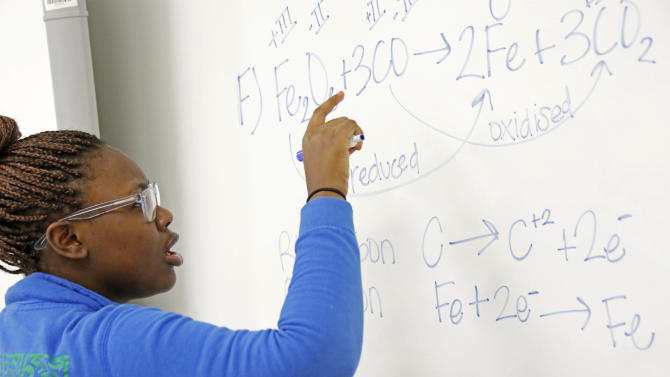 In this Feb. 15, 2013 photograph, Clarksdale High School student Shamia Hopper works on a chemical equation at the dry marker board in her Clarksdale, Miss., classroom. City  leaders hope improved education will help stanch a hemorrhaging population. The city's nine public schools may also be the crossroads of Mississippi's education system as state lawmakers are considering a new route, one characterized by charter schools, teacher merit pay, a tougher statewide curriculum, state-paid preschool classes and an intensive focus on reading for young students. (AP Photo/Rogelio V. Solis)