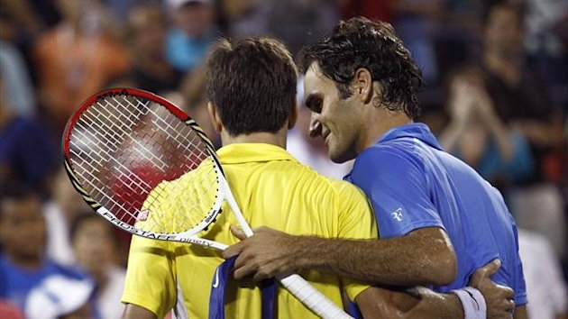 Roger Federer of Switzerland (R) and Tommy Robredo of Spain embrace at the net after Robredo defeated Federer in three sets at the U.S. Open tennis championships in New York September 2, 2013 (Reuters)