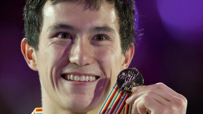 Canada's Patrick Chan shows his gold medal in the men's competition at the World Figure Skating Championships Friday, March 15, 2013 in London, Ontario. (AP Photo/The Canadian Press, Paul Chiasson)