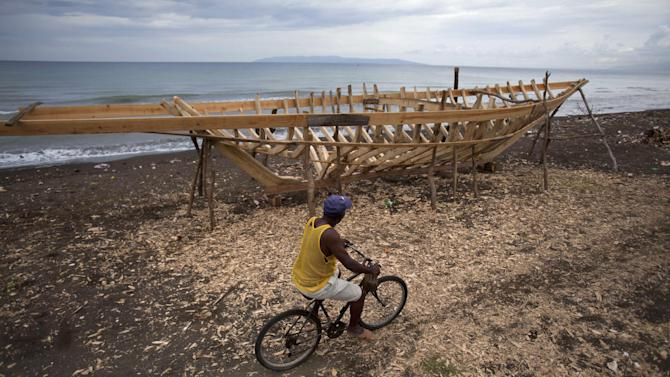 In this May 4, 2013 photo, a man rides on his bicycle past the frame of a sailboat under construction in Leogane, Haiti. The 30-foot-long boats, whose frames resemble the rib cage of a small dinosaur, are purchased by smugglers for around $12,000 and then taken to northern Haiti to find passengers.  In another major migration trend, Brazil also has become an increasingly common destination for Haitians since the 2010 earthquake.  (AP Photo/Dieu Nalio Chery)