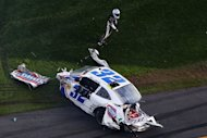 Kyle Larson gets out of his destroyed car following a crash at Daytona International Speedway on February 23, 2013. Larson, making his first start in NASCAR&#39;s second-tier series, was launched into the catch-fencing in a smash near the end of the race