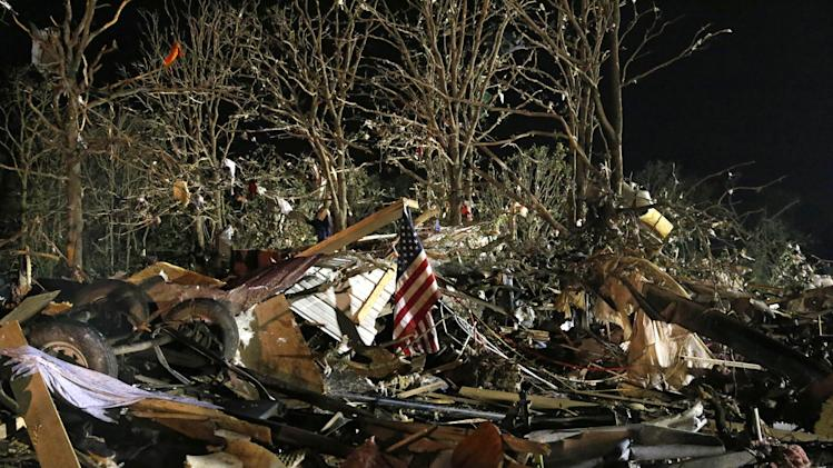 A flag flies in the debris of a mobile home after a tornado struck a mobile home park near Dale, Okla., Sunday, May 19, 2013. (AP Photo Sue Ogrocki)