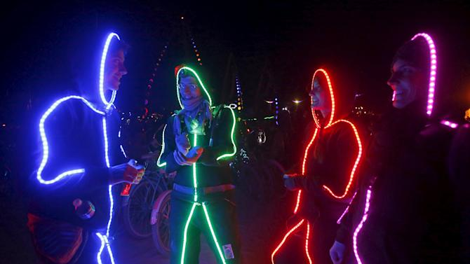 "A group of participants wear illuminated suits during the Burning Man 2015 ""Carnival of Mirrors"" arts and music festival in the Black Rock Desert of Nevada"