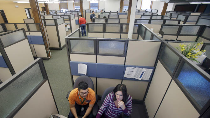 FILE - In this Sept. 27, 2013 file photo, MNsure contact center representatives specialist Carlos Villanueva, left, and guide Emily Joyce work in one many cubicles at the center in St. Paul, Minn. in preparation for Oct. 1, 2013 when the state's new online portal for delivering changes tied to the federal health care law opens for enrollment. Minnesota's efforts became so beset with problems that Democratic Gov. Mark Dayton issued a public apology and MNsure's top executive resigned in December 2013. (AP Photo/Jim Mone,File)