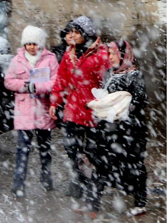 Syrian women walk through the streets of central Damascus during snow fall on January 9, 2013 as a fierce storm whipped the region this week and temperatures dropped dramatically.   AFP PHOTO/ STR