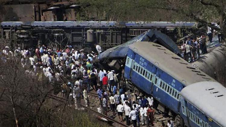 People gather around a passenger train that derailed near Roha station, 110 kilometers (70 miles) south of Mumbai, Maharashtra state, India, Sunday, May 4, 2014. The cause of the accident was not immediately known. (AP Photo)
