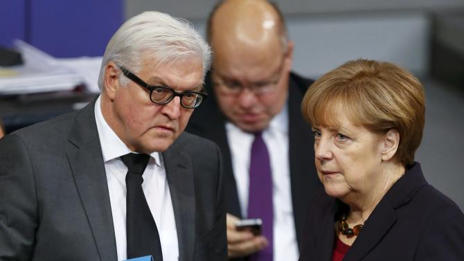 German Chancellor Merkel speaks to Foreign Minister Steinmeier as they stand behind Economy Minister Gabriel during a session of the lower house of parliament Bundestag in Berlin