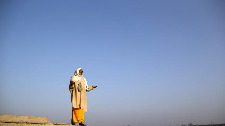 A Hindu man worships the Sun god Surya on the banks of the river Yamuna in New Delhi