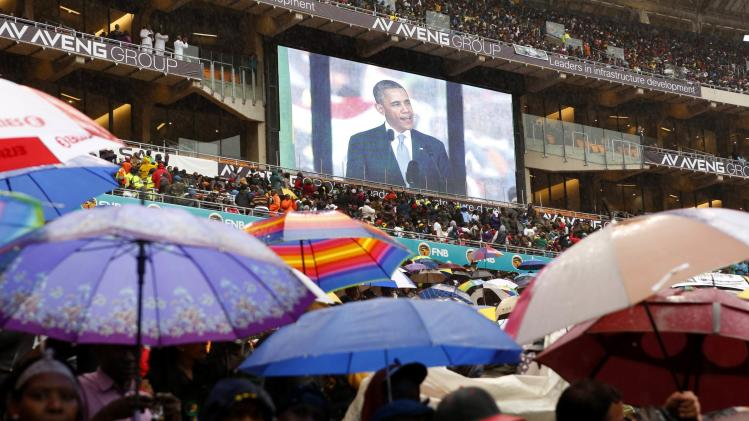 South Africans brave the rain as they listen to U.S. President Obama speaking during a memorial service for Mandela in Johannesburg