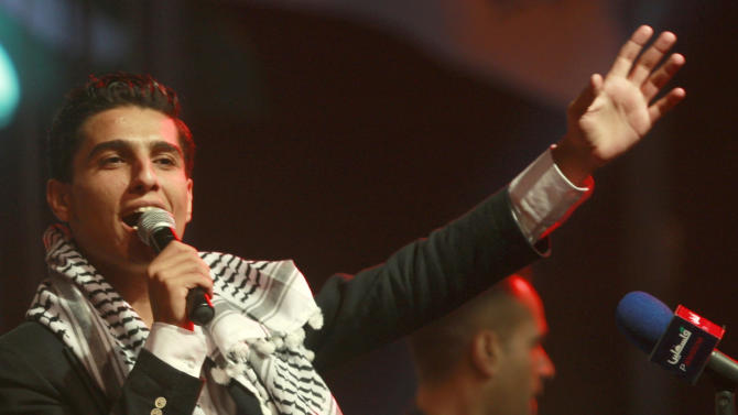 """File - In this July 1, 2013 file photo, Mohammed Assaf, the 23-year-old from the Gaza Strip who won the popular pan-Arab song contest """"Arab Idol"""" last month performs in the West Bank city of Ramallah. Fame has opened a door for a former Gaza wedding singer that remains closed for others in the blockaded territory: Mohammed Assaf, winner of the popular TV talent contest Arab Idol, gets to move to the West Bank. The West Bank and Gaza lie on either side of Israel. Citing security reasons, Israel has severely restricted movement between the two territories for more than a decade.(AP Photo/Majdi Mohammed, File)"""