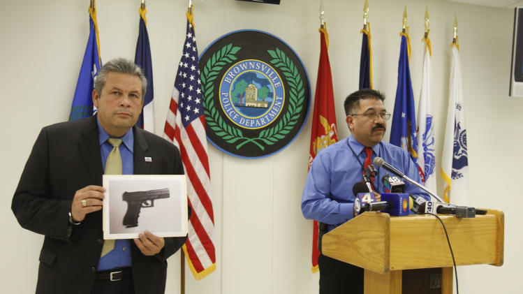 Brownsville city manager Charlie Cabler, left, holds up a photo of the carbon dioxide powered pellet handgun 15-year-old Jaime Gonzalez was holding at the time he was shot by police at Cummings Middle School as Police Chief Orlando Rodriguez speaks during a news conference Wednesday, Jan. 4, 2012 in Brownsville, Texas. (AP Photo/The Brownsville Herald, Yvette Vela)