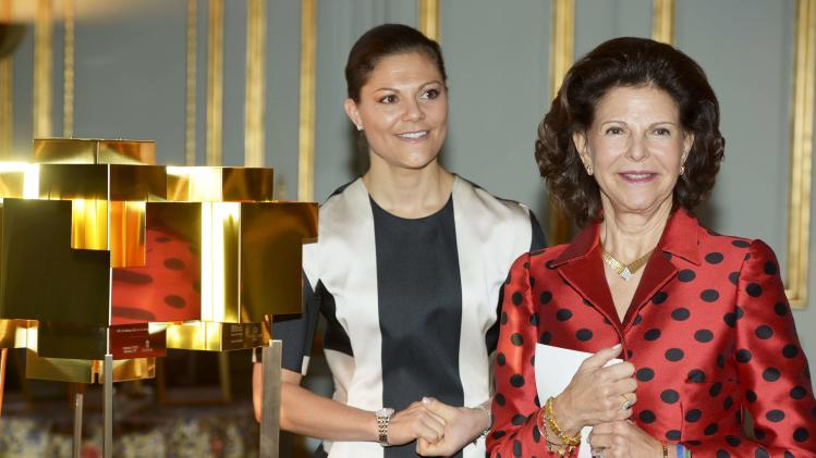 Queen Silvia and Crown Princess Victoria pose with a floor lamp, a gift from the Swedish parliament, during a reception in Stockholm