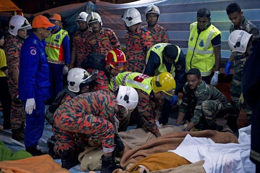 Malaysian rescuers wrap the bodies of bus passengers killed in an accident near the Genting Highlands, August 21, 2013