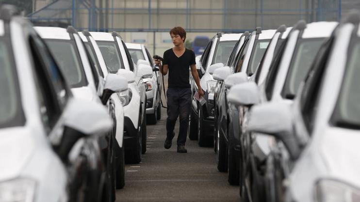 A worker checks cars made by GM Korea in a yard of GM Korea's Bupyeong plant in Incheon
