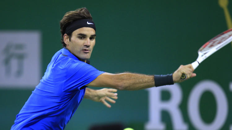 Roger Federer of Switzerland returns the ball against his compatriot Stanislas Wawrinka during the third round match of the Shanghai Masters tennis tournament at Qizhong Forest Sports City Tennis Center in Shanghai, China, Thursday, Oct. 11, 2012. Federer won 4-6 7-6(4), 6-0. (AP Photo/Eugene Hoshiko)
