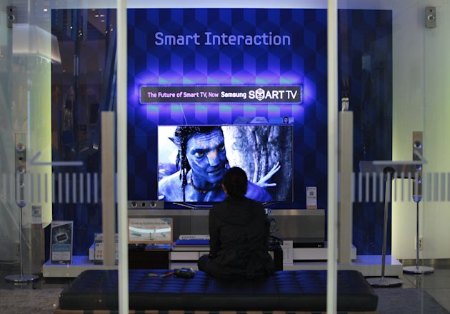 A shopper looks at Samsung Electronics' smart television at its showroom in Seoul, South Korea, Friday, April 27, 2012. Samsung Electronics Co., the world's largest consumer electronics firm by revenues, on Friday reported a record-high profit as strong smartphone sales helped mask a drop in semiconductor and TV profit. Net profit amounted to 5.05 trillion won ($4.46 billion) for the fiscal quarter ending March 31, compared with 2.78 trillion won a year earlier. (AP Photo/Ahn Young-joon)