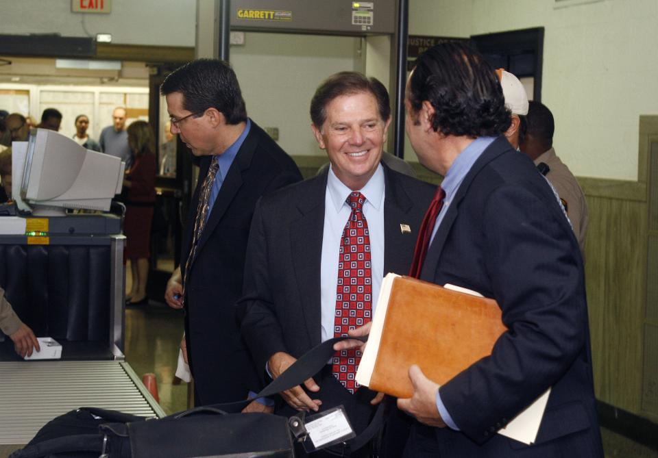 Former House Majority Leader Tom DeLay, center,  arrives at the Travis County courthouse in Austin, Texas on Tuesday, Oct. 26, 2010 for jury selection in his corruption trial. The 63-year-old DeLay is charged with money laundering and conspiracy to commit money laundering. (AP Photo/Jack Plunkett)