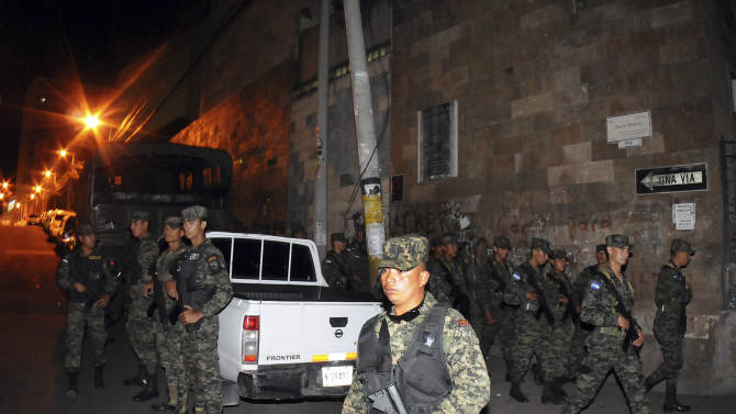 Honduras army soldiers secure the area outside of the National Congress in the capital city of Tegucigalpa, Honduras, Tuesday Dec. 11, 2012. The Honduran congress approved a bill Tuesday to submit President Porfirio Lobo's police cleanup program to a popular vote, after the measure was blocked by the courts. (AP Photo/Fernando Antonio)