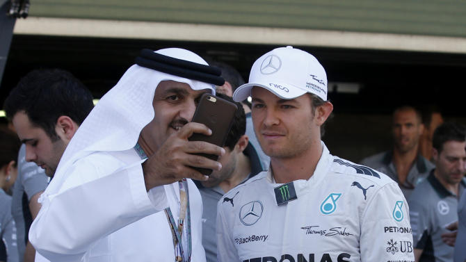An Emirati fan takes a selfie with Mercedes driver Nico Rosberg of Germany prior to the start of the Emirates Formula One Grand Prix at the Yas Marina racetrack in Abu Dhabi, United Arab Emirates, Sunday, Nov. 23, 2014. (AP Photo/Luca Bruno)