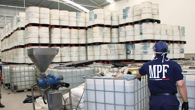 "FILE - In this June 20, 2011, photo released by Mexico's Attorney General's office, police from the Federal Public Ministry looks at drums of precursor chemicals for methamphetamine that were seized in Queretaro, Mexico. Mexican drug cartels are flooding U.S. cities with cheap, extraordinarily pure methamphetamine made in factory-like ""super labs"" _ a surge in production that has all but negated the nation's long effort to curb meth production at home with tighter controls on key ingredients.(AP Photo/Attorney General's office, File)"