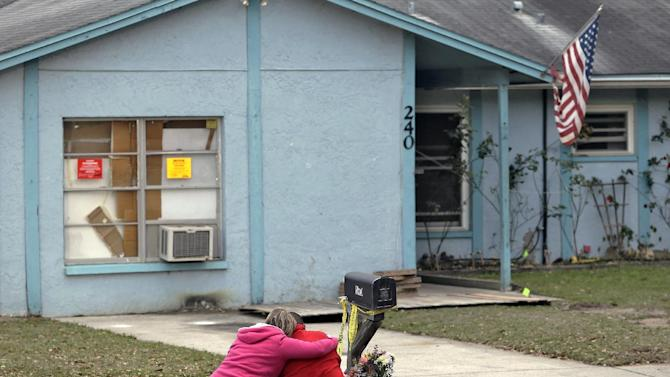 Jeremy Bush, right, is consoled by an unidentified woman Sunday, March 3, 2013, as he sits outside a home where a sinkhole opened up underneath a bedroom late Thursday evening, swallowing his brother, Jeffrey Bush, in Seffner, Fla. Crews on Sunday began the demolition of the Florida home.  (AP Photo/Chris O'Meara)