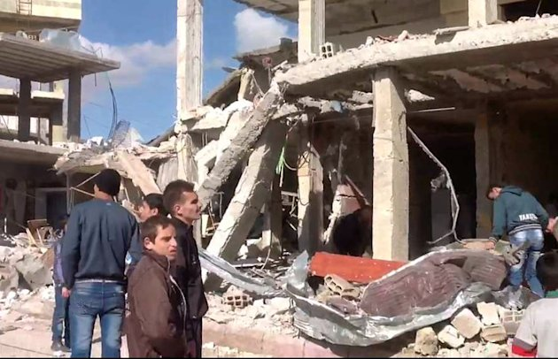 In this photo released by the Syrian official news agency SANA, Syrian citizens gather in front of a damaged building destroyed by a car bomb in Qatana, (25) kilometers (15 miles) southwest of Damascus, Syria, Thursday, Dec. 13, 2012. A bomb blast near a school in a Damascus suburb killed more than a dozen people, at least half of them women and children, the state news agency reported. Russia, Syria's most important international ally, said for the first time that President Bashar Assad is increasingly losing control and the opposition may win the civil war. (AP Photo/SANA)