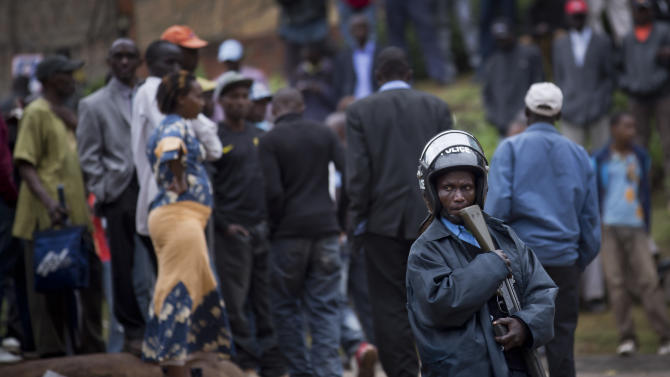 A Kenyan policeman keeps crowds of onlookers back from the Westgate Mall, in Nairobi, Kenya Monday, Sept. 23, 2013. Four large blasts rocked Kenya's Westgate Mall on Monday, sending large plumes of smoke over an upscale suburb as Kenyan military forces sought to rescue an unknown number of hostages held by al-Qaida-linked militants. (AP Photo/Ben Curtis)
