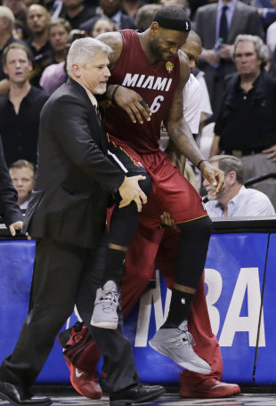 LeBron James needs help to get to the bench in the fourth quarter of Thursday's NBA Finals opener. (AP)