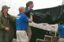 In this image taken from video provided by Fox35 News, a SeaWorld rescue team (in blue shirts) removes a shark from a truck that ran off a highway in Oak Hill, Fla., Wednesday, June 10, 2015. Authorities say a shark was killed in a Florida traffic accident when a truck carrying four of the big fish blew a tire and ran off the highway. The Florida Highway Patrol says the four sharks were being driven to an aquarium in New York City from Marathon, Florida, when the tractor-trailer transporting them ran off of Interstate 95 near Oak Hill.The SeaWorld rescue team from Orlando moved the remaining sharks to its facility until transportation arrangements can be made. (Fox35 News via AP)