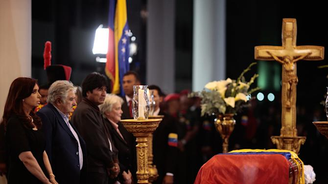 In this photo released by Miraflores Press Office, Argentina's President Cristina Fernandez, left, Uruguay's President Jose Mujica, second from left, Bolivia's President Evo Morales, third from left, and Mujica's wife, Uruguayan Senator Lucía Topolansky stand next to the flag-draped coffin containing the body of Venezuela's late President Hugo Chavez on display during his wake in Fort Tiuna military academy where his body will lie in state in Caracas, Venezuela, Wednesday, March 6, 2013. Seven days of mourning were declared, all schools were suspended for the week and friendly heads of state were expected for an elaborate funeral Friday. (AP Photo/Miraflores Presidential Press Office)