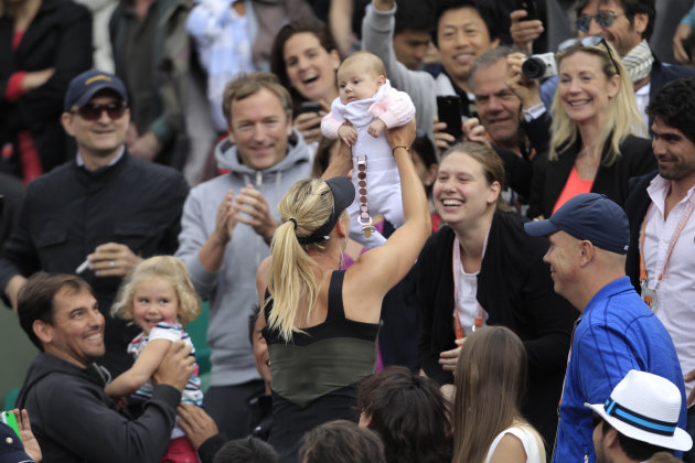 Maria Sharapova of Russia holds an unidentified baby after winning the women's final match against Sara Errani of Italy at the French Open tennis tournament in Roland Garros stadium in Paris, Saturday