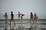 File picture. Men play football near the Kaladan river in Sittwe, Myanmar, in June. Political developments give reason for hope for the future of football in the country, with formerly isolated Myanmar's opening-up to the outside world expected to bring extra sponsorship