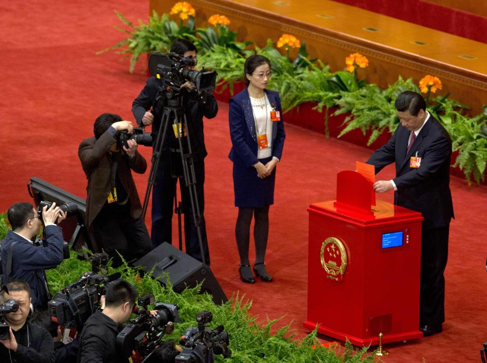 Chinese Communist Party chief and incoming-President Xi Jinping casts his votes at a plenary session of the National People's Congress where delegates are expected to elect Xi officially as president at the Great Hall of the People in Beijing Thursday, March 14, 2013. (AP Photo/Ng Han Guan)