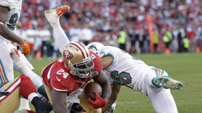 San Francisco 49ers running back Anthony Dixon carries the ball into the end zone for a touchdown on a one-yard run past Miami Dolphins safety Tyrone Culver, right, during the third quarter of an NFL football game in San Francisco, Sunday, Dec. 9, 2012. (AP Photo/Marcio Jose Sanchez)