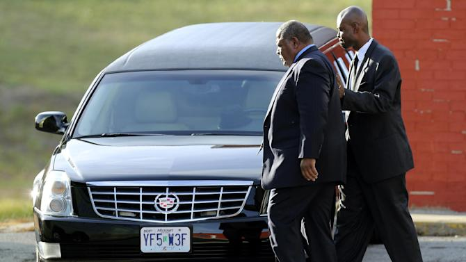 Kansas City Chiefs head coach Romeo Crennel, left, leaves a memorial service for Jovan Belcher at the Landmark International Deliverance and Worship Center, Wednesday, Dec. 5, 2012, in Kansas City, MoO. Belcher shot his girlfriend, Kasandra Perkins, at their home Saturday morning before driving to Arrowhead Stadium and turning the gun on himself. (AP Photo/Ed Zurga)