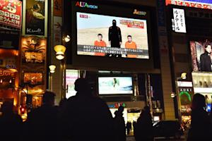 Tokyo residents look at news reports about two Japanese …