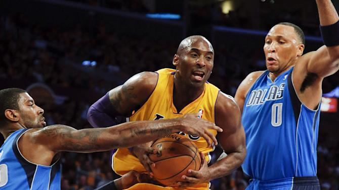 Los Angeles Lakers' Kobe Bryant, center, is defended by Dallas Mavericks' O.J. Mayo, left, and Shawn Marion in the first half of an NBA basketball game in Los Angeles, Tuesday, Oct. 30, 2012. (AP Photo/Jae C. Hong)