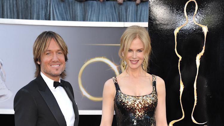 "FILE - This Feb. 24, 2013 file photo shows musician Keith Urban, left, and his wife actress Nicole Kidman at the Oscars at the Dolby Theatre in Los Angeles. urban is a judge on the singing competition series, ""American Idol,"" airing Wednesdays and Thursdays on Fox. (Photo by John Shearer/Invision/AP, file)"