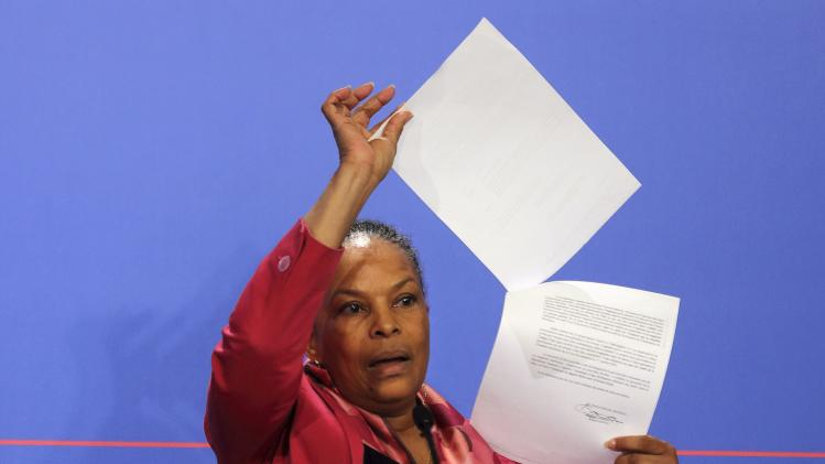 French Justice minister Christiane Taubira holds copies of the wiretapping memos during a news conference at the Elysee Palace in Paris