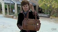 Ginger Littleton holds up the brown bag she used as a weapon to attack the gunman who'd taken a school board hostage. (CNN via Daily Mail)
