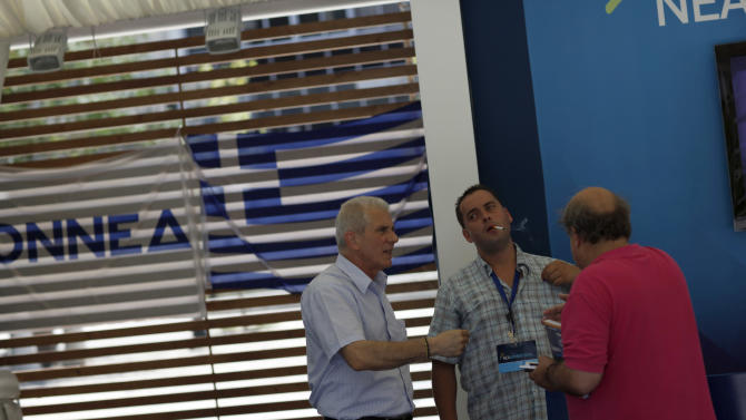 """Supporters of Conservative """"New Democracy"""" party chat inside an election kiosk one day before general elections in Athens, Saturday, June 16, 2012. Greeks vote for the second time in six weeks Sunday amid fears that the country could be forced out of the euro if they reject the strict austerity measures taken in return for billions of euros in rescue loans from other European countries and the International Monetary Fund. (AP Photo/Kostas Tsironis)"""