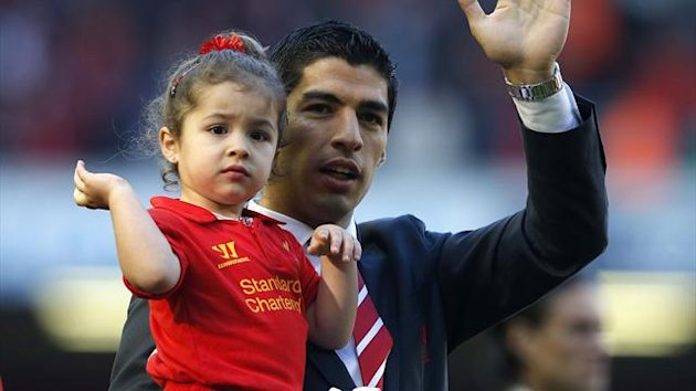 Liverpool's Luis Suarez carries his daughter around the Anfield pitch at the end of the season (Reuters)