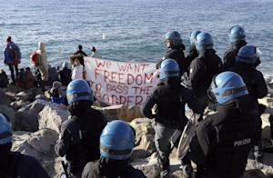 Refugees and migrants face Italian police officers…