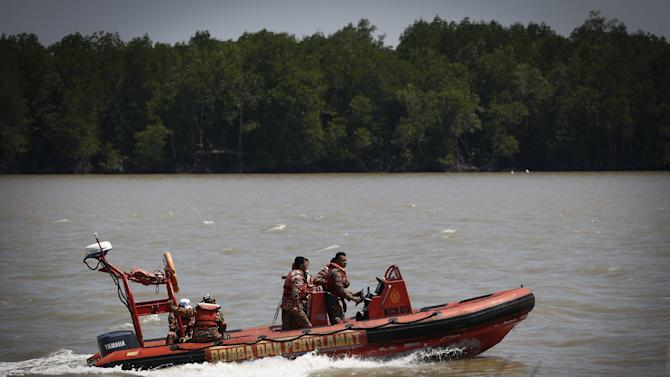 Malaysian Search and rescue personnel on a speed boat search for passengers of a sunken boat in outskirt of Banting, Malaysia, Wednesday, June 18, 2014. A wooden boat carrying more than 90 Indonesian migrants capsized and sank after leaving Malaysia's west coast, and rescuers scrambled to save more than 60 people still missing, Malaysia's maritime agency said Wednesday. (AP Photo/Vincent Thian)