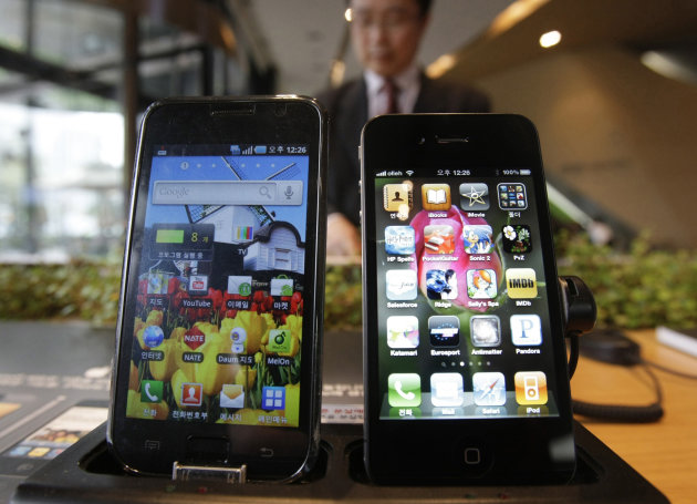 FILE-In this Friday, April 22, 2011, file photo, Samsung Electronics' Galaxy S, left, and Apple's iPhone 4 are displayed at the headquarters of South Korean mobile carrier KT in Seoul, South Korea, Friday. In a preliminary move, a federal judge denied Friday, Sept. 14, 2012, Samsung's request for a ban on imports of the iPhone, iPad and iPod. A judge at the International Trade Commission in Washington ruled Friday that Apple doesn't violate four Samsung patents. (AP Photo/Ahn Young-joon, File)