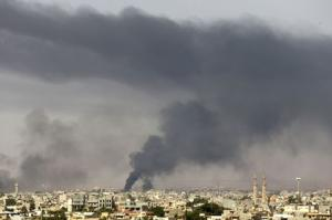 Black plumes of smoke is seen in the vicinity of Camp Thunderbolt, after clashes between militants, former rebel fighters and government forces in Benghazi
