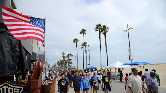 People walk on the Venice Beach boardwalk in Los Angeles on August 4, 2013